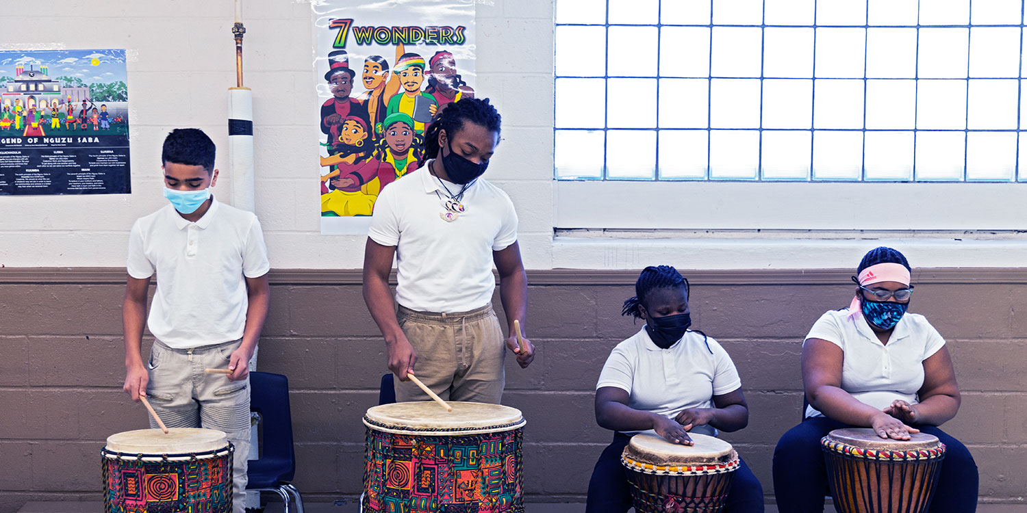Students playing African drums.