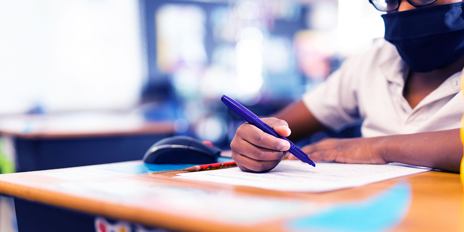 Close up of student's hand holding a marker over paper while sitting at a desk.