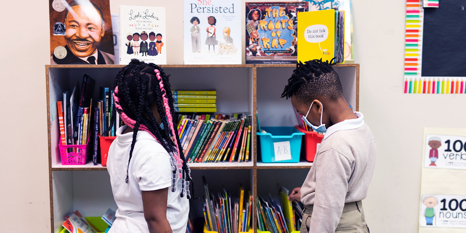 Students in front of bookshelf selecting books.