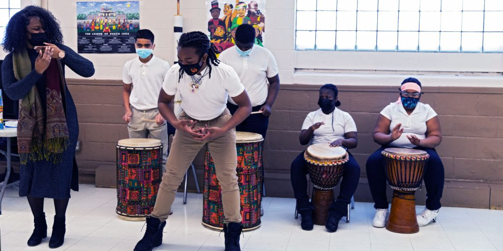 Students playing African drums and teacher and student doing African dance.